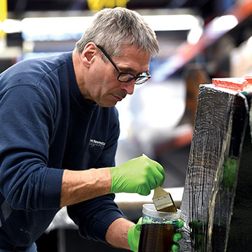 WeeGee Smith of Vermont SportsCar applies resin to a radiator duct mold.