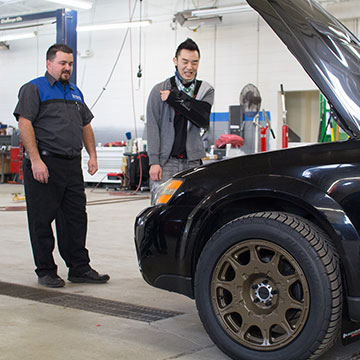 Frank Romano, left, and Isaac Katz, right, take a look at the modded Outback. From fixing axles to adding new wheels, Subaru employees came together to mod Katz's Outback for daily use.