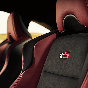 The Alcantara-upholstered seats are embroidered with tS identification, and the ample side bolsters are accented with red leather.